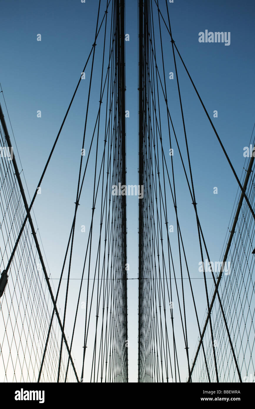 Iron support wires of suspension bridge against blue sky, low angle view - Stock Image