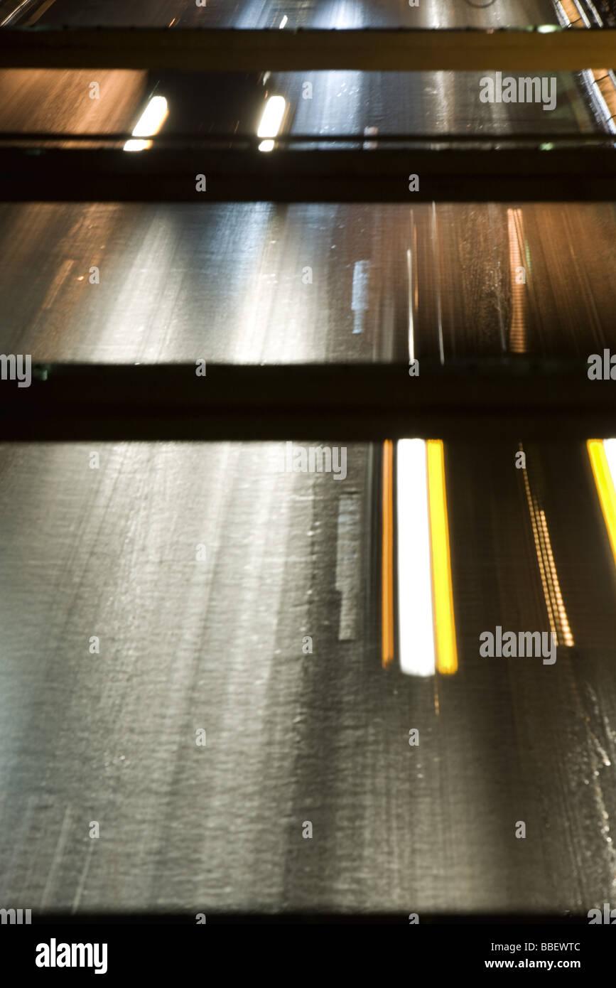 Headlights of oncoming traffic speeding along freeway, high angle view - Stock Image
