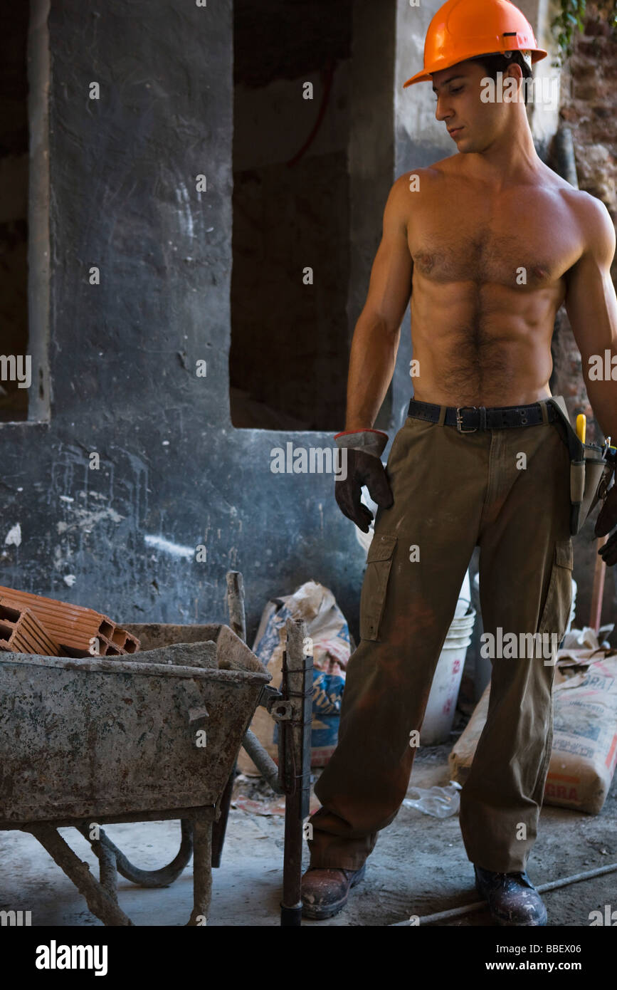 Barechested construction worker standing near wheelbarrow at construction site - Stock Image