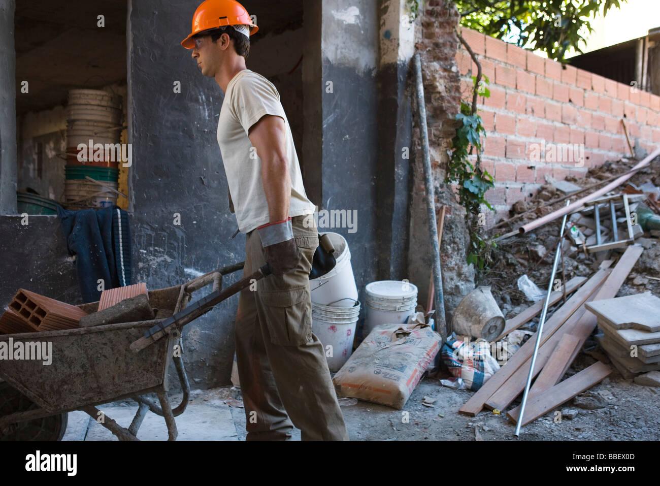 Construction worker moving wheelbarrow through construction site - Stock Image