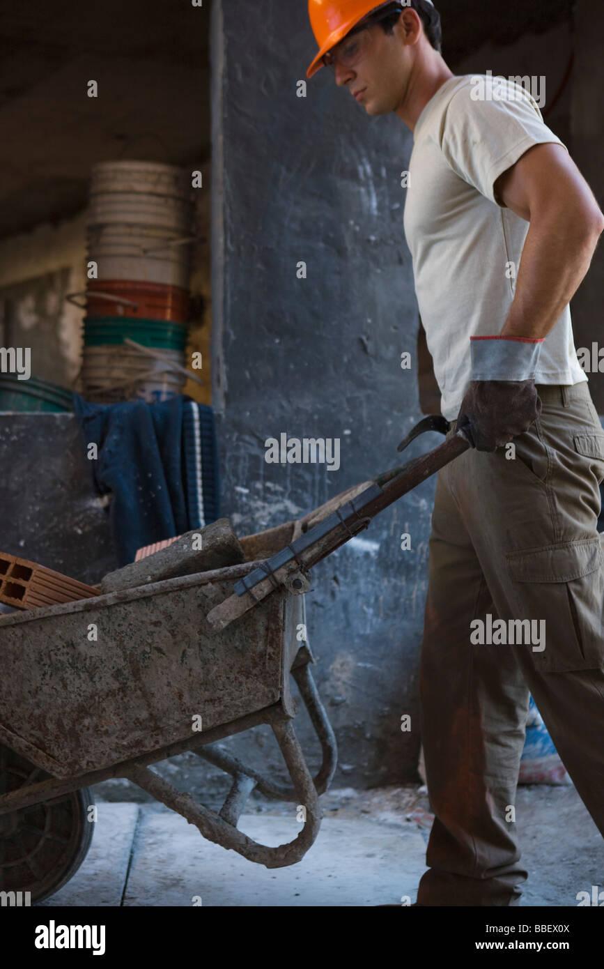 Construction worker pushing wheelbarrow through construction site - Stock Image