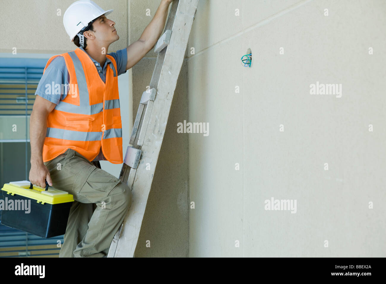 Man climbing ladder carrying toolboxStock Photo