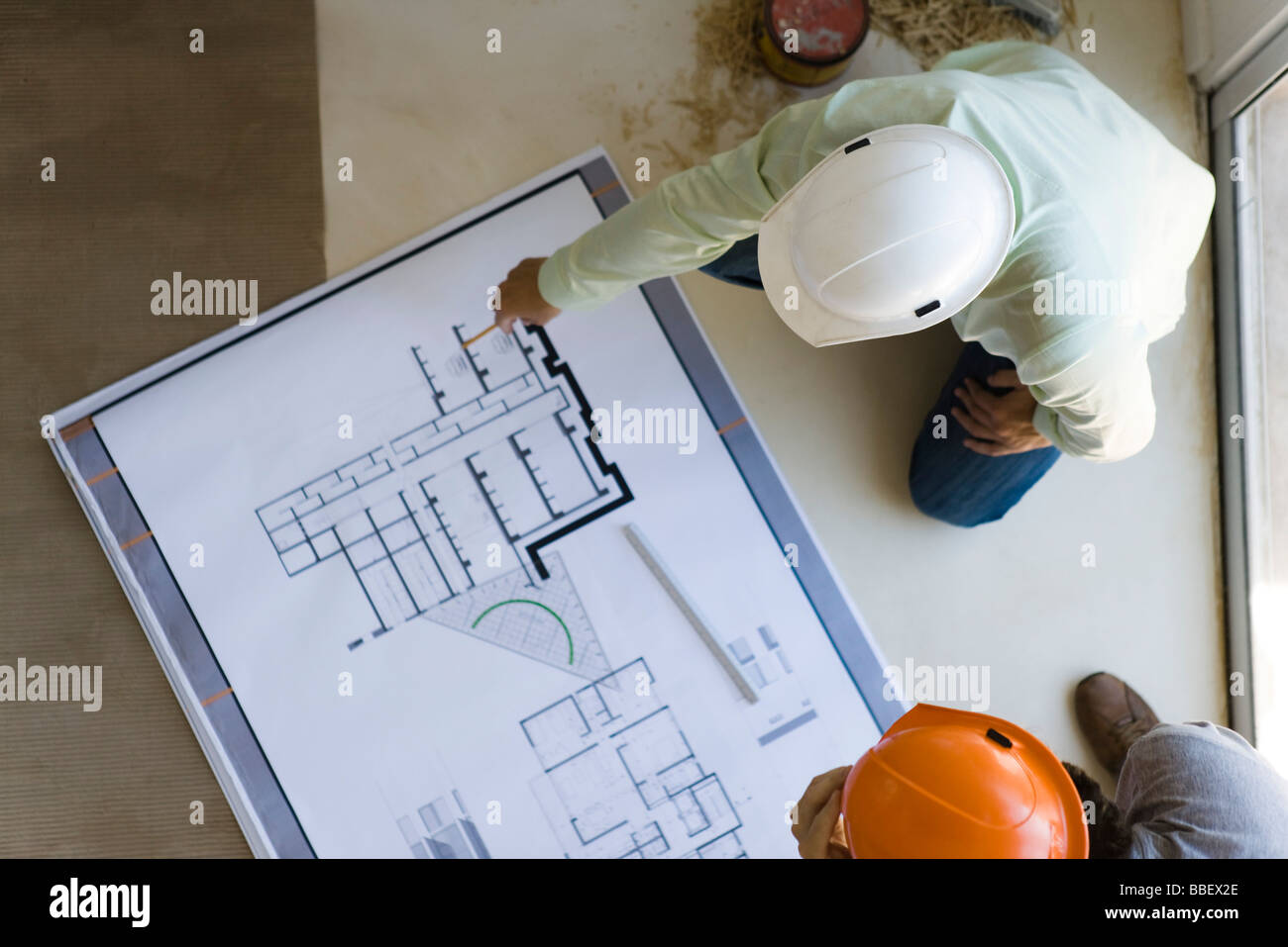 Two men reviewing blueprint spread out on floor - Stock Image