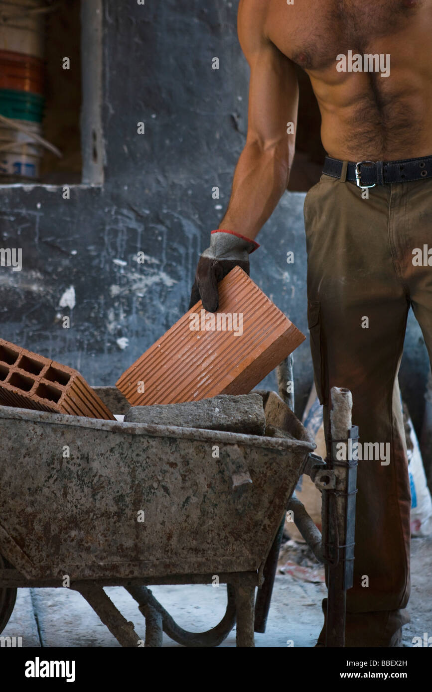 Barechested construction worker placing brick in wheelbarrow - Stock Image