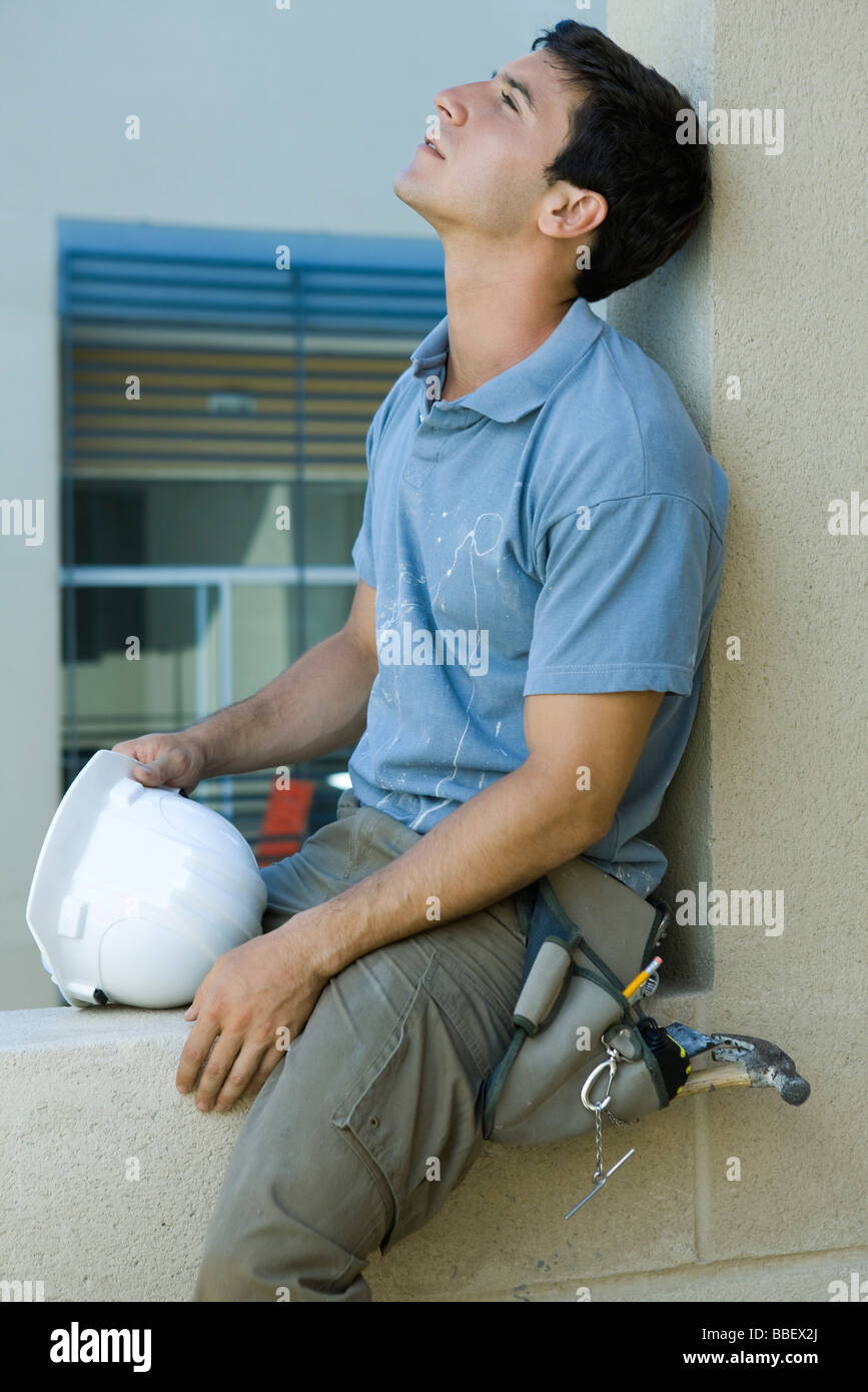 Man sitting on ledge, leaning head back, looking up - Stock Image