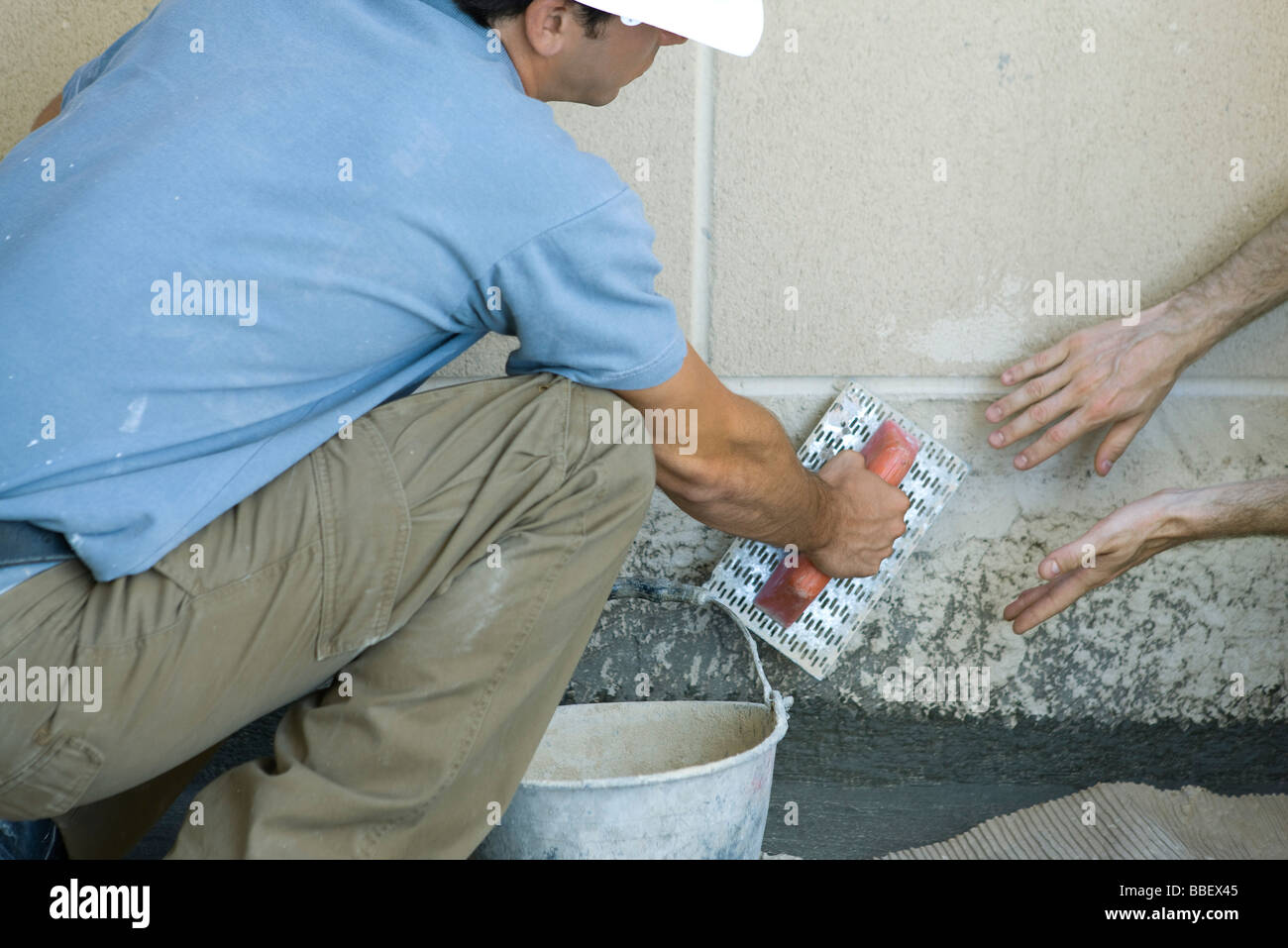 Mason receving guidance on proper masonry technique - Stock Image
