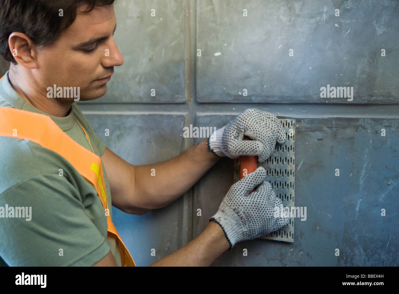 Mason with towel smoothing wall surface, close-up - Stock Image