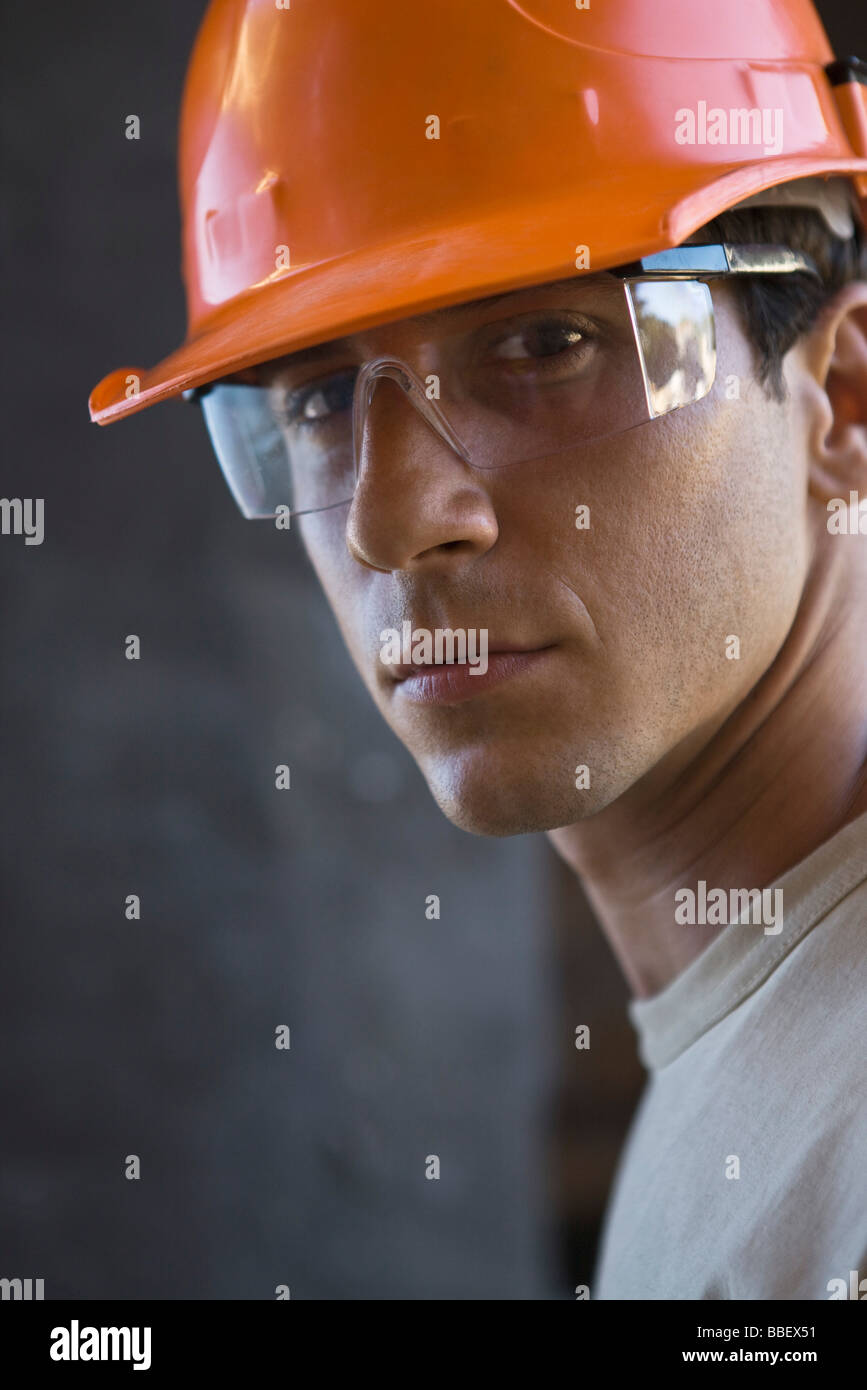 construction worker wearing hard hat protective glasses looking at