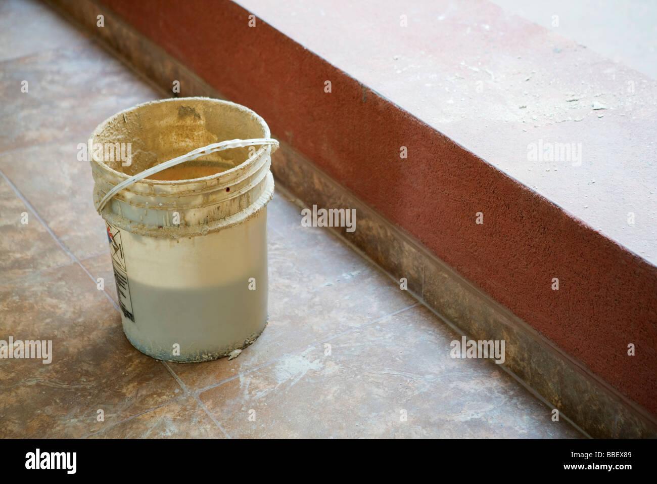Bucket set on tiled floor near ledge - Stock Image