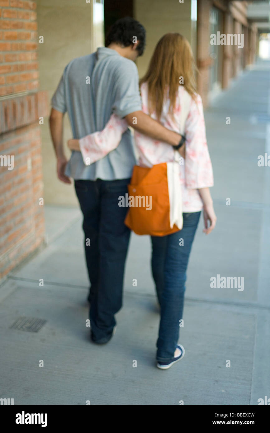 Young couple walking with arms around each other's waists, rear view - Stock Image