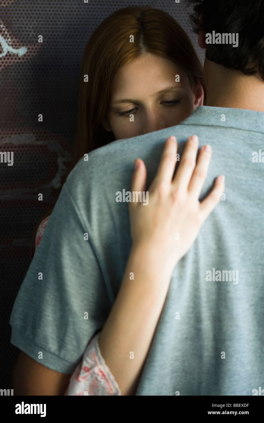 Young couple embracing stiffly, woman looking down Stock Photo