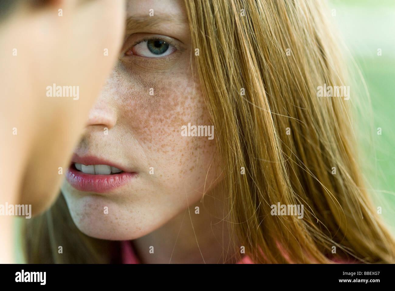 Young woman facing man, staring warily at camera, cropped - Stock Image