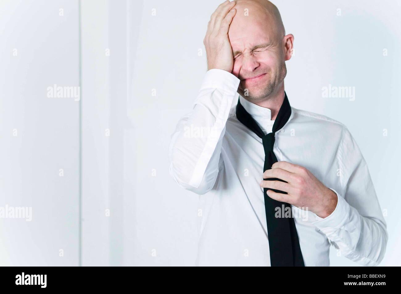 Businessman loosening his tie - Stock Image