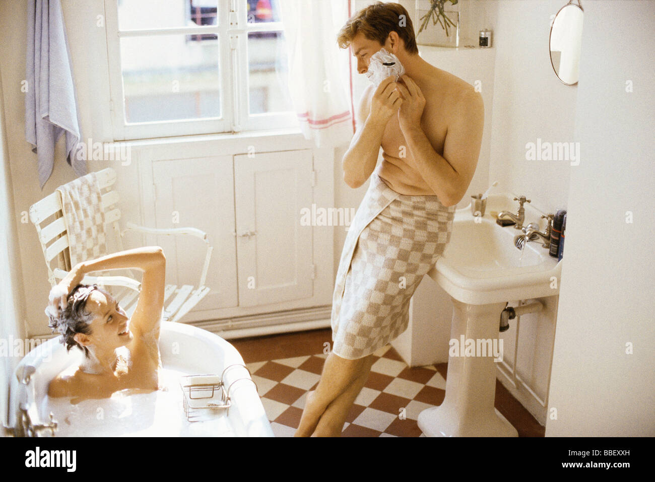 Couple together in bathroom, woman bathing, man leaning against sink, shaving - Stock Image