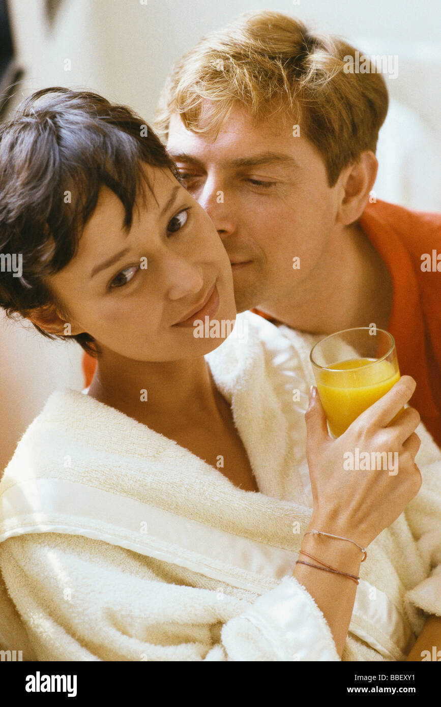 Woman holding glass of orange juice, man kissing her cheek - Stock Image