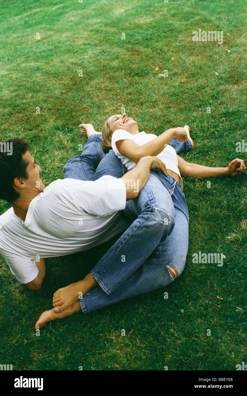 Couple reclining on ground together, laughing, high angle view - Stock Image