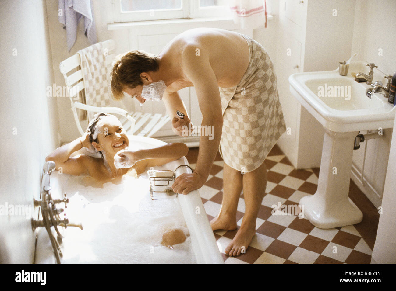 Couple together in bathroom, woman in bathtub, man leaning over her with shaving cream on face - Stock Image