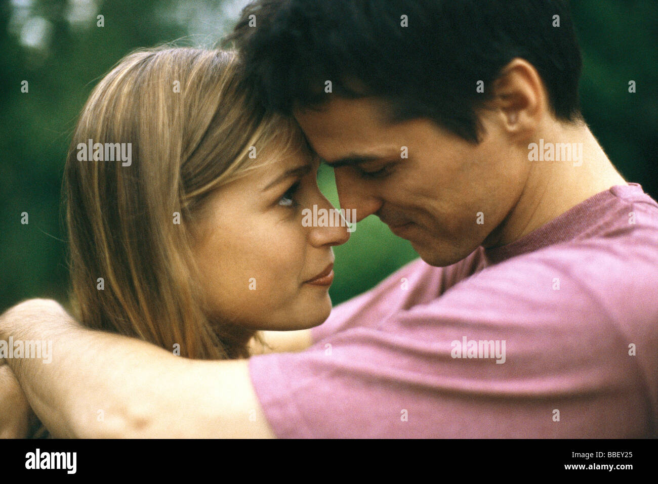 Couple embracing, touching foreheads, side view - Stock Image