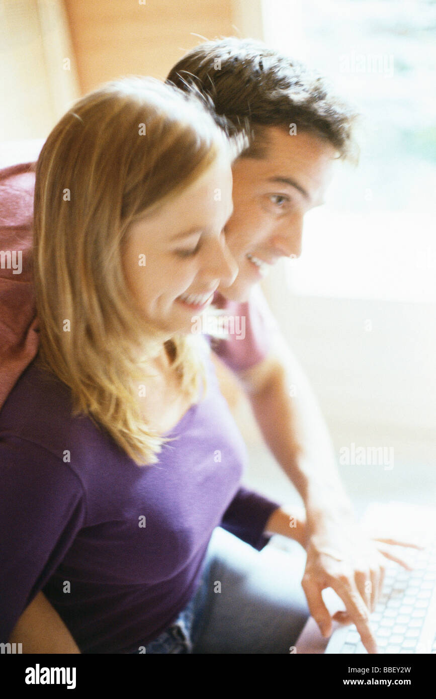 Couple typing on keyboard together, man leaning over woman's shoulder - Stock Image