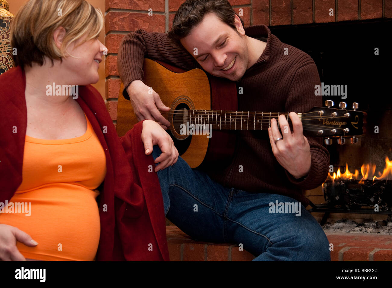 A happy father plays the guitar for his pregnant wife - Stock Image