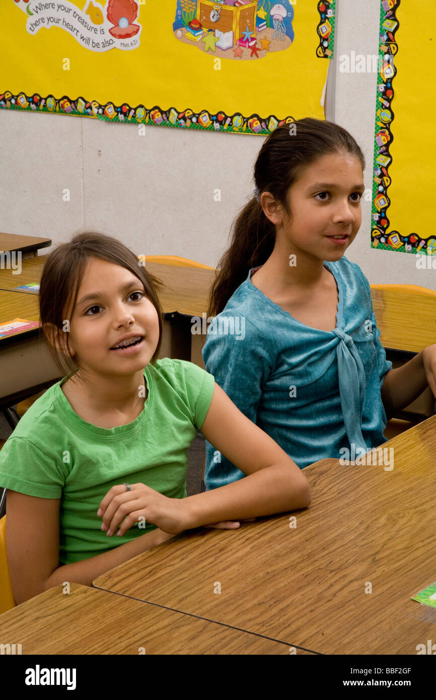 Two young Hispanic ethnic multi girls 8-9 year old olds United States sitting and talking  listening in classroom - Stock Image
