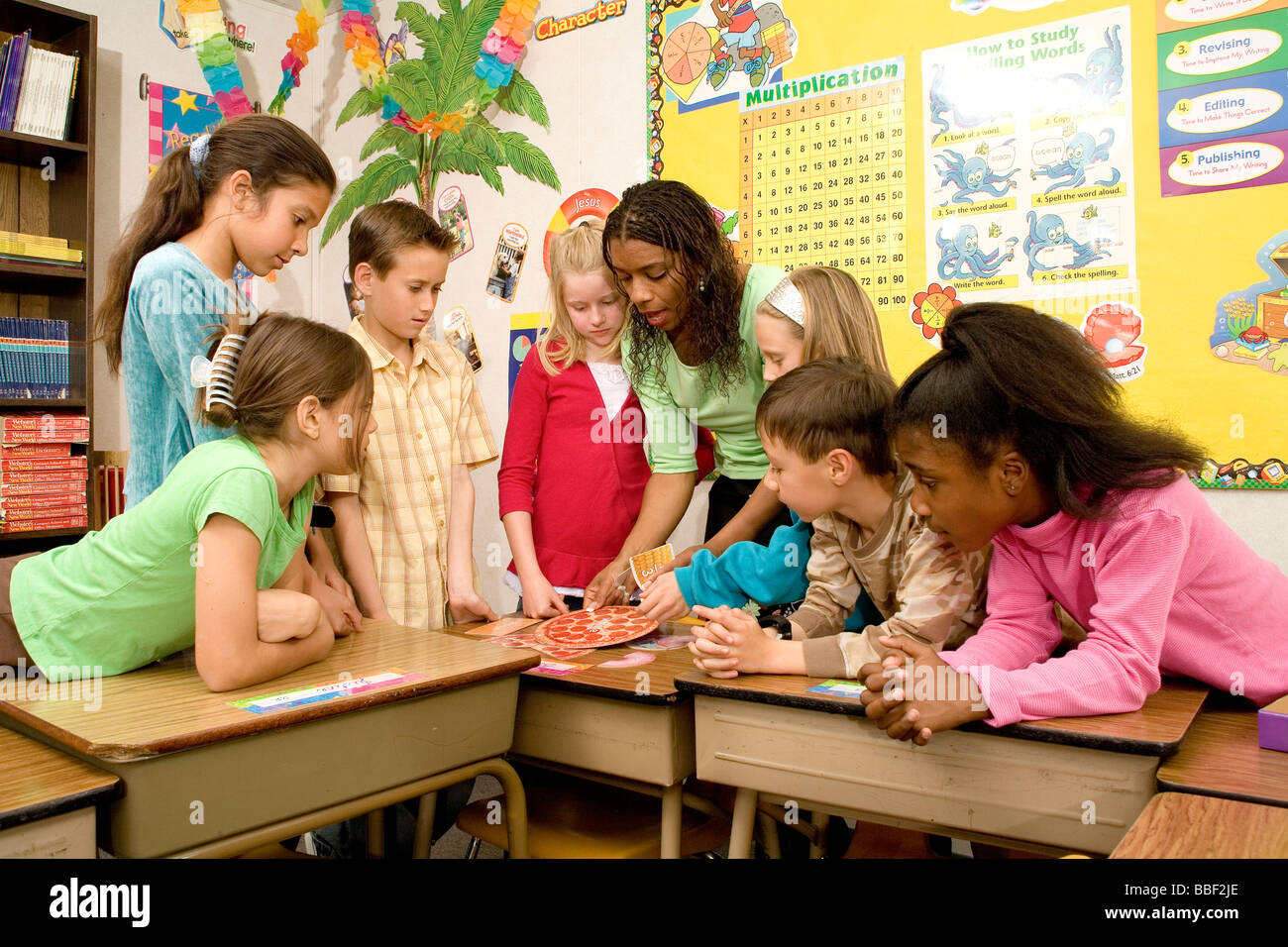 multi interracial diverse interracial Teacher teaching children grouped together 8-10 year old primary school  classroom - Stock Image