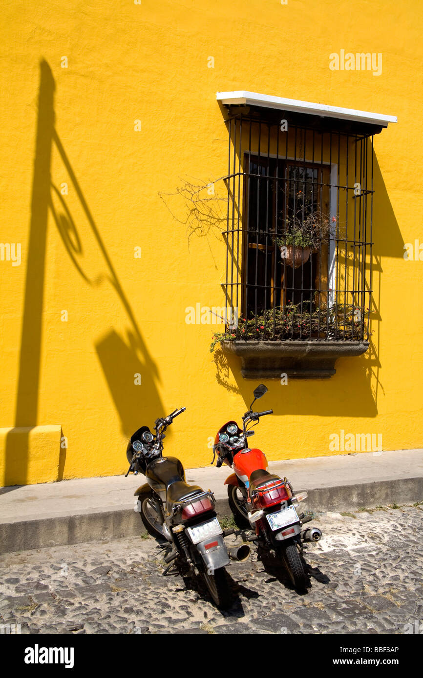 Antigua, Guatemala, Central America; Motorcycles parked outside restaurant - Stock Image