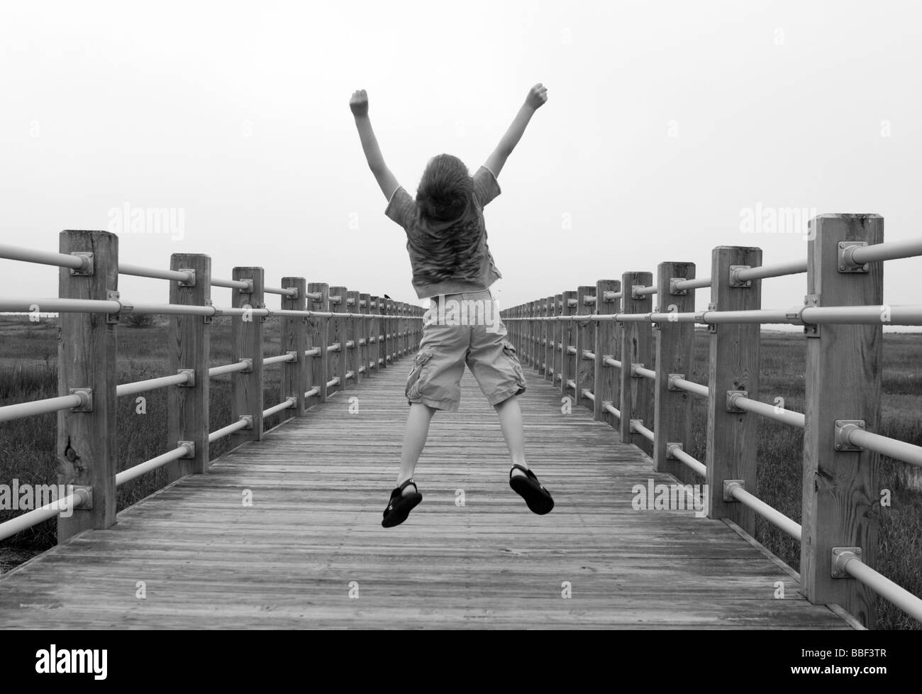 I child jumps with joy along a boardwalk in Milford Connecticut USA - Stock Image