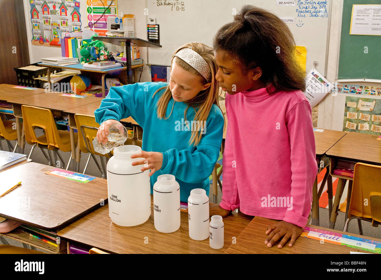 Two focused girls 8-9 year old pouring fluid contanier children inter racial  racially diverse multicultural cultural Stock Photo