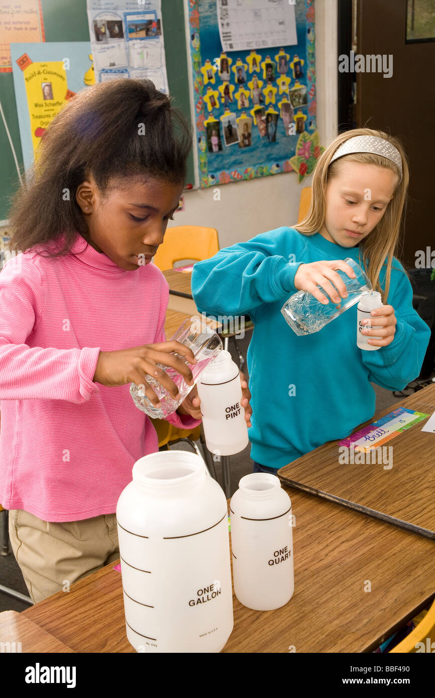 Two school children 8-9 year old working together pour fluid multi ethnic racial  racially diverse multicultural Stock Photo
