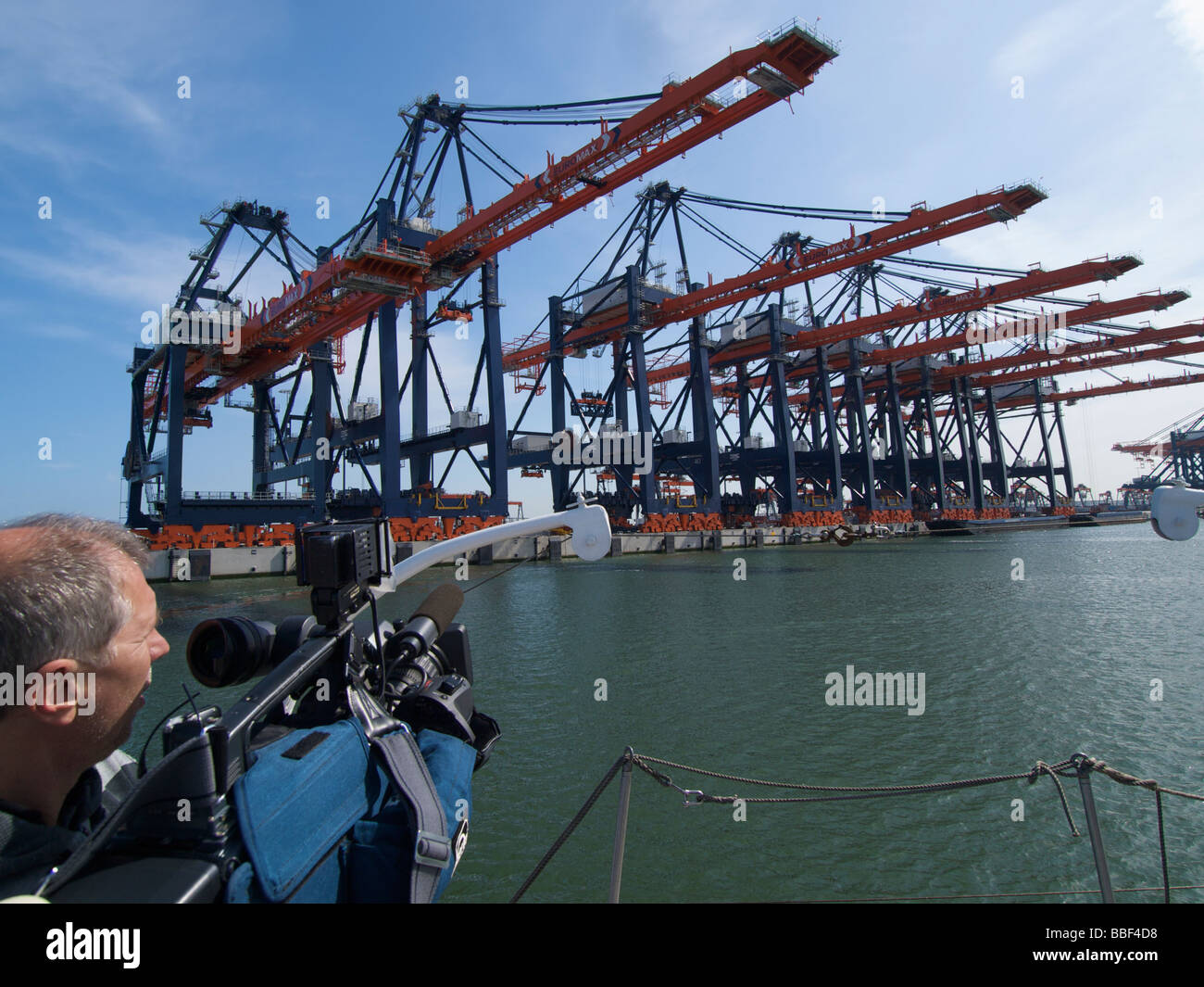 TV cameraman filming empty container terminal in the port of Rotterdam to show the global economic crisis the Netherlands - Stock Image