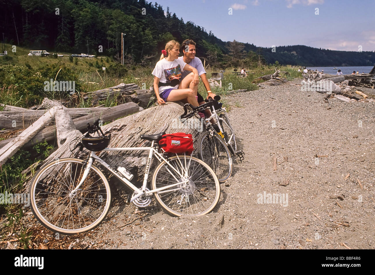 Man and woman bicycle riders take a break at Possession Point Whidbey Island WA USA - Stock Image