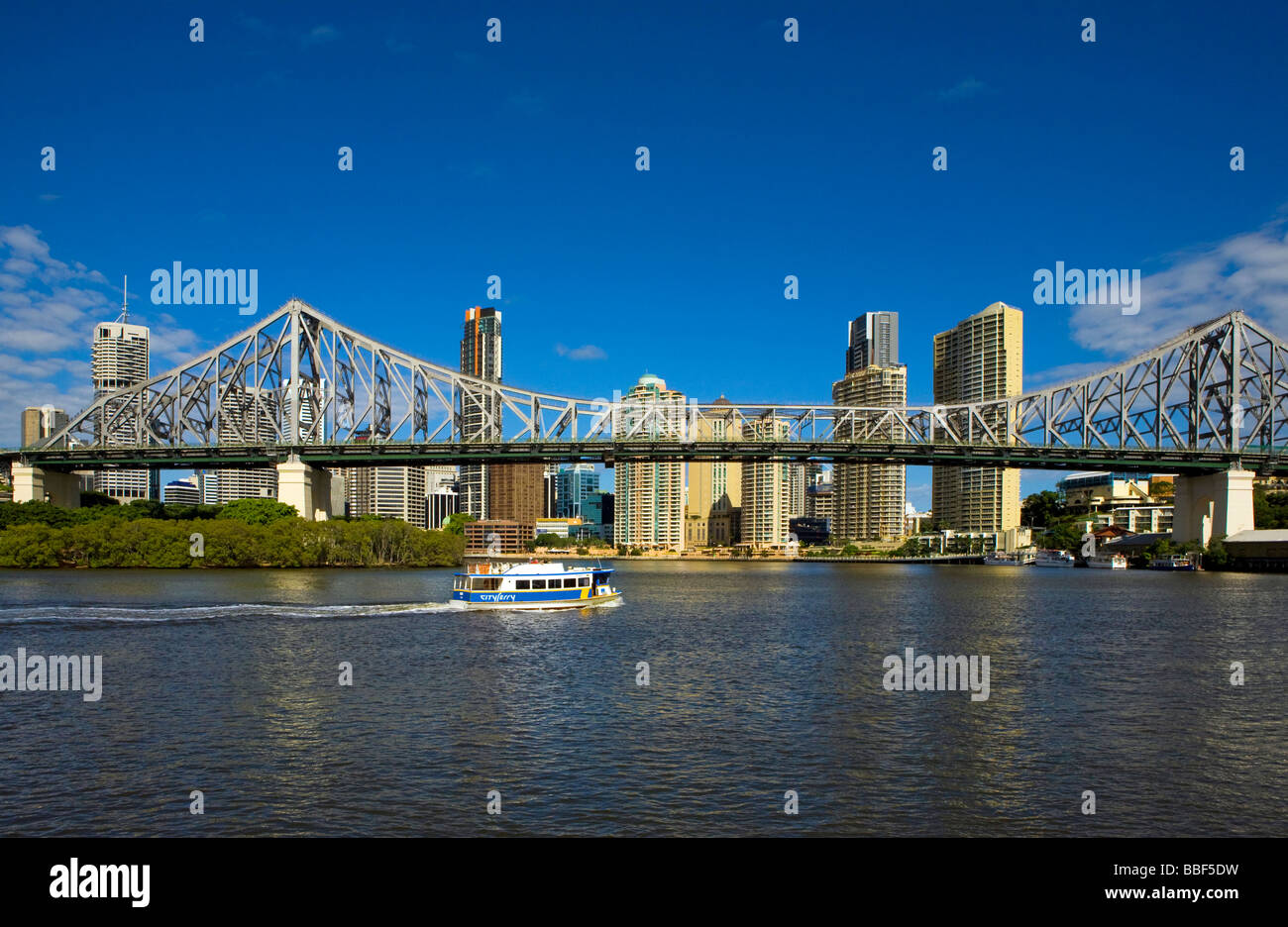 Australia, Queensland, Brisbane. City Ferry goes under the Story Bridge with Brisbane skyline - Stock Image
