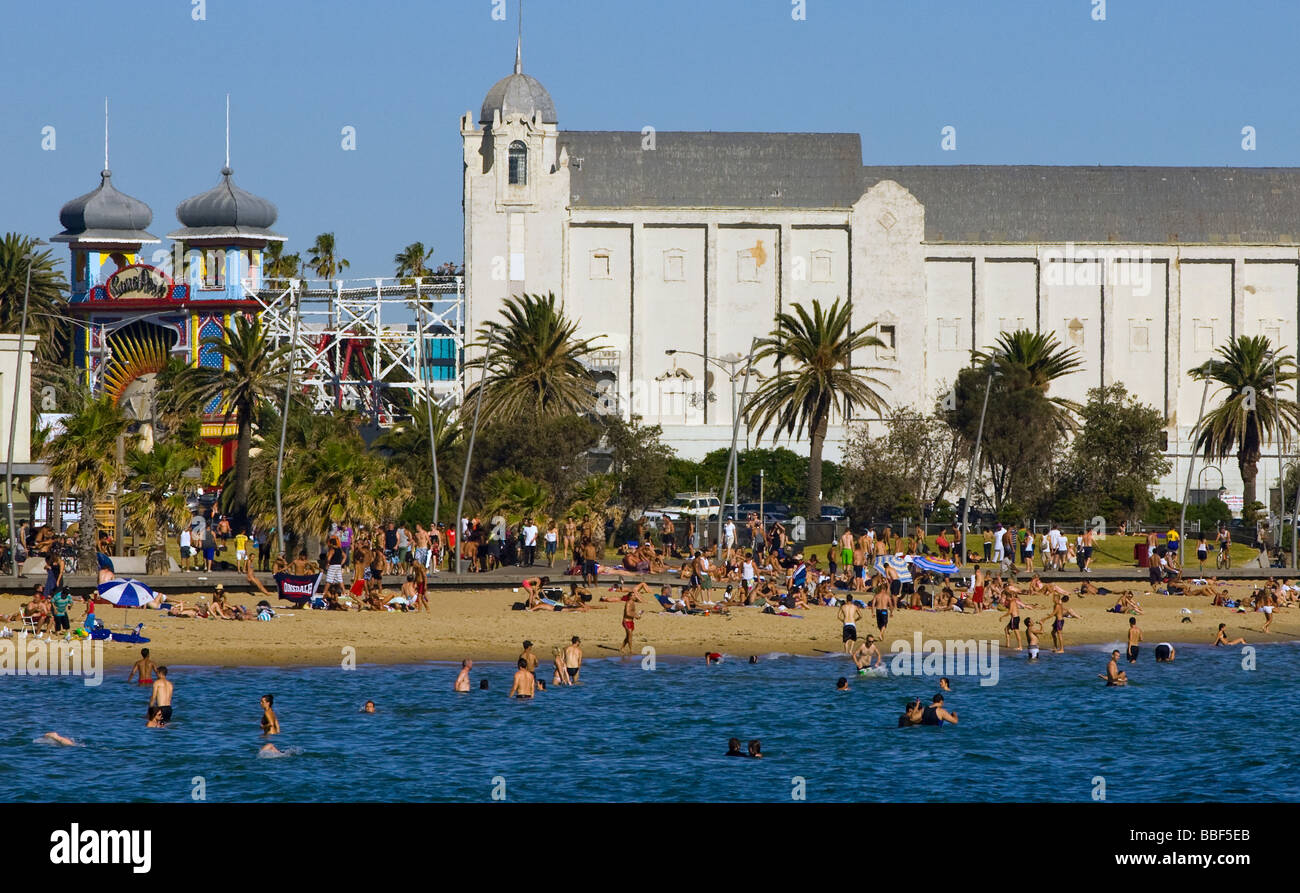 Australia, Victoria, Melbourne, St Kilda. People on St Kilda Beach with the Palais Theatre and Luna Park behind. - Stock Image