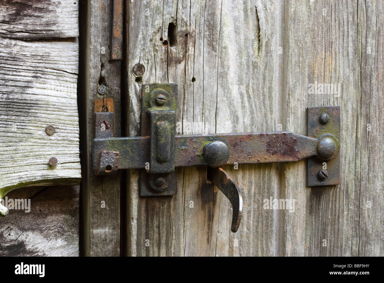 Latch and lock on old shed door. - Stock Image