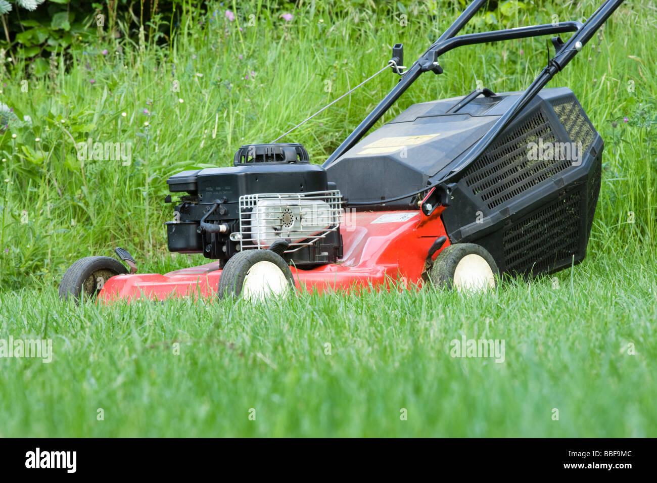 Lawnmower in long grass. - Stock Image