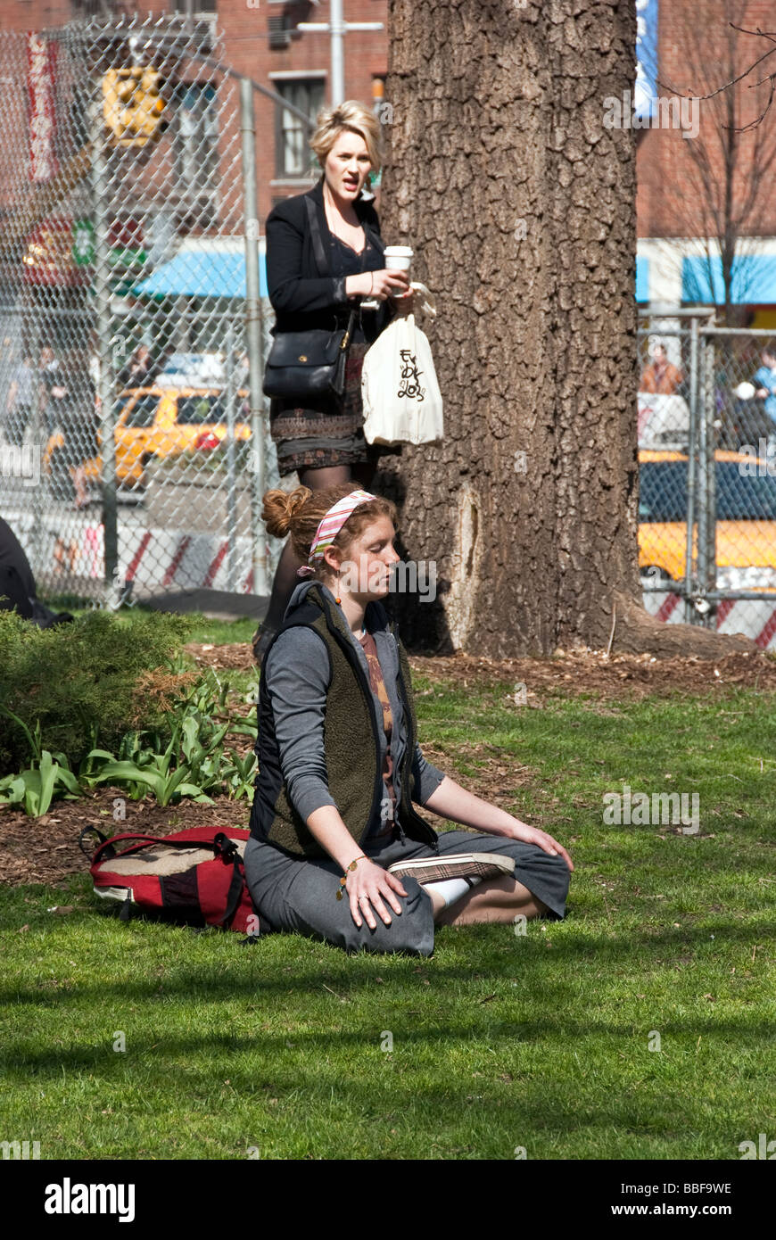 a young red haired woman with rosy cheeks & freckles sits cross-legged meditating in Union Square Park, New - Stock Image