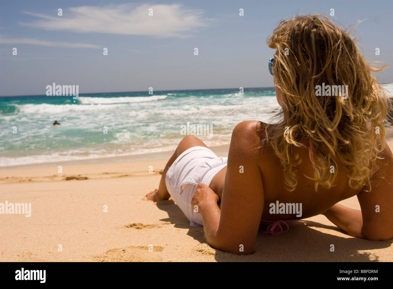 A girl lied down on the sand - Stock Image