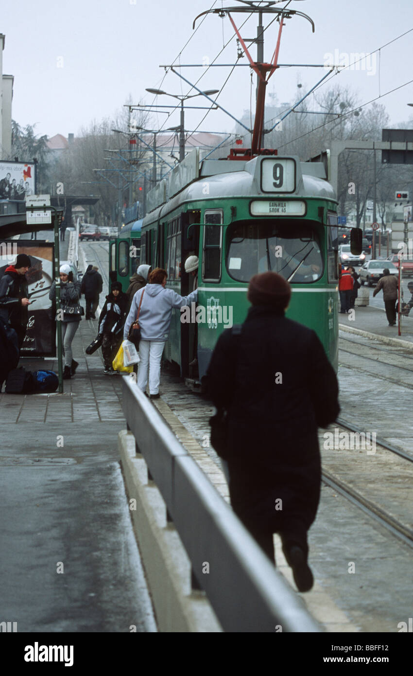Public streetcar with boarding and deboarding people at a stopover in Belgrade in winter, Serbia, Balkans - Stock Image