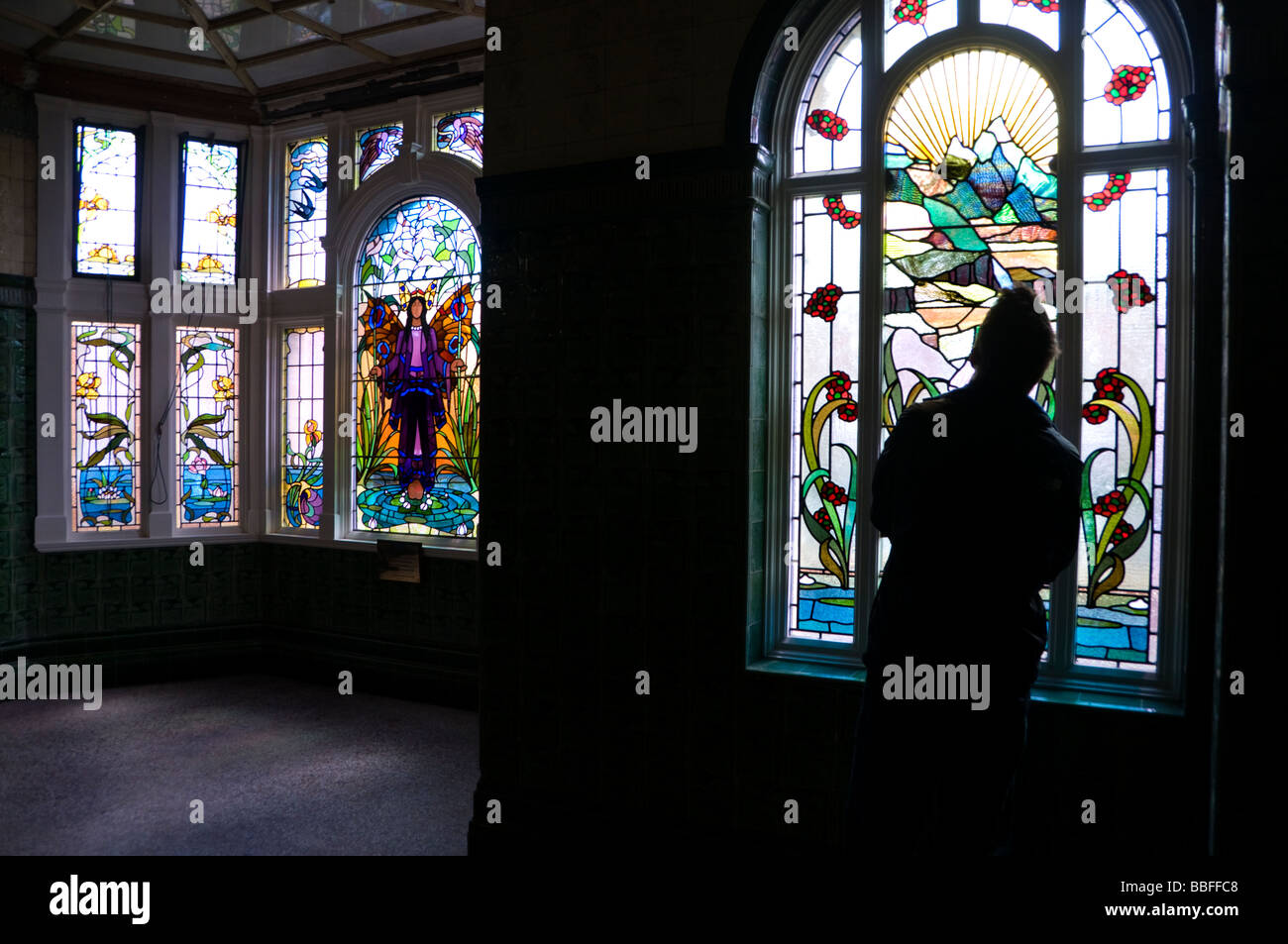 A visitor looking at a stained glass window inside Victoria Baths, Manchester, England, UK - Stock Image