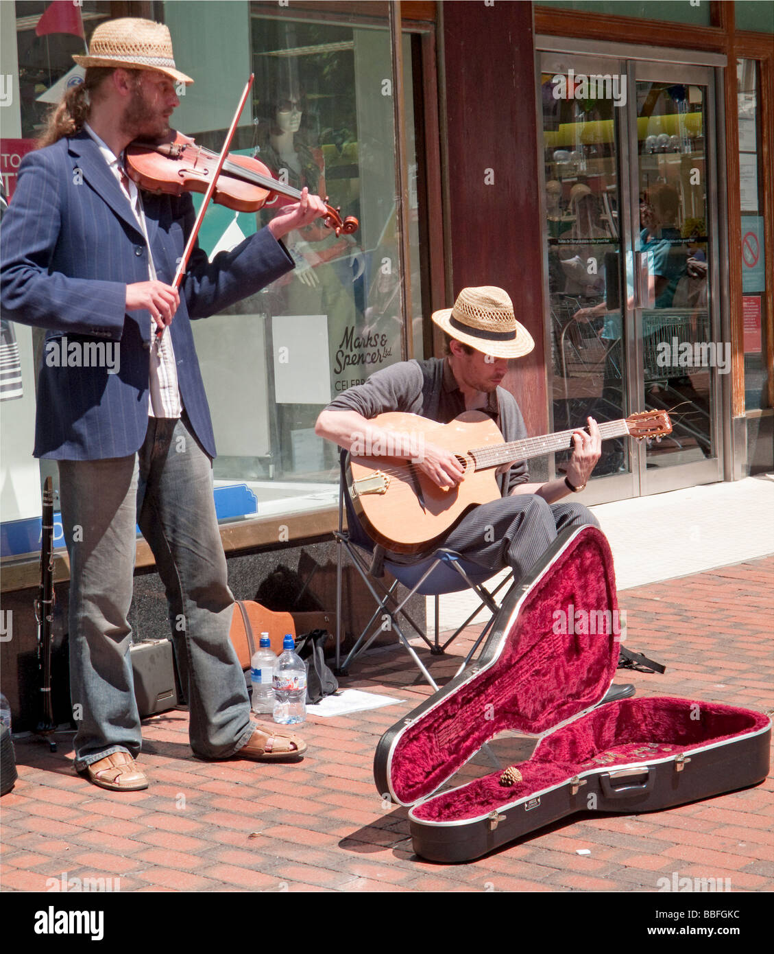 Two buskers play in a street in the sun - Stock Image