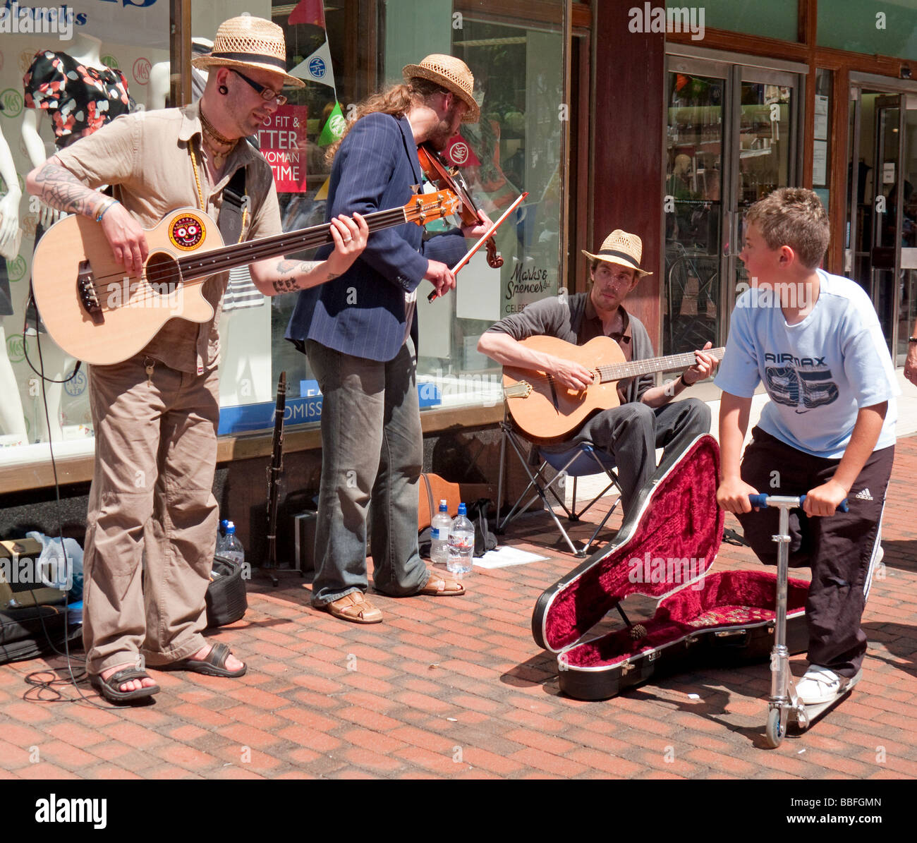 Three buskers play in a street in the sun - Stock Image