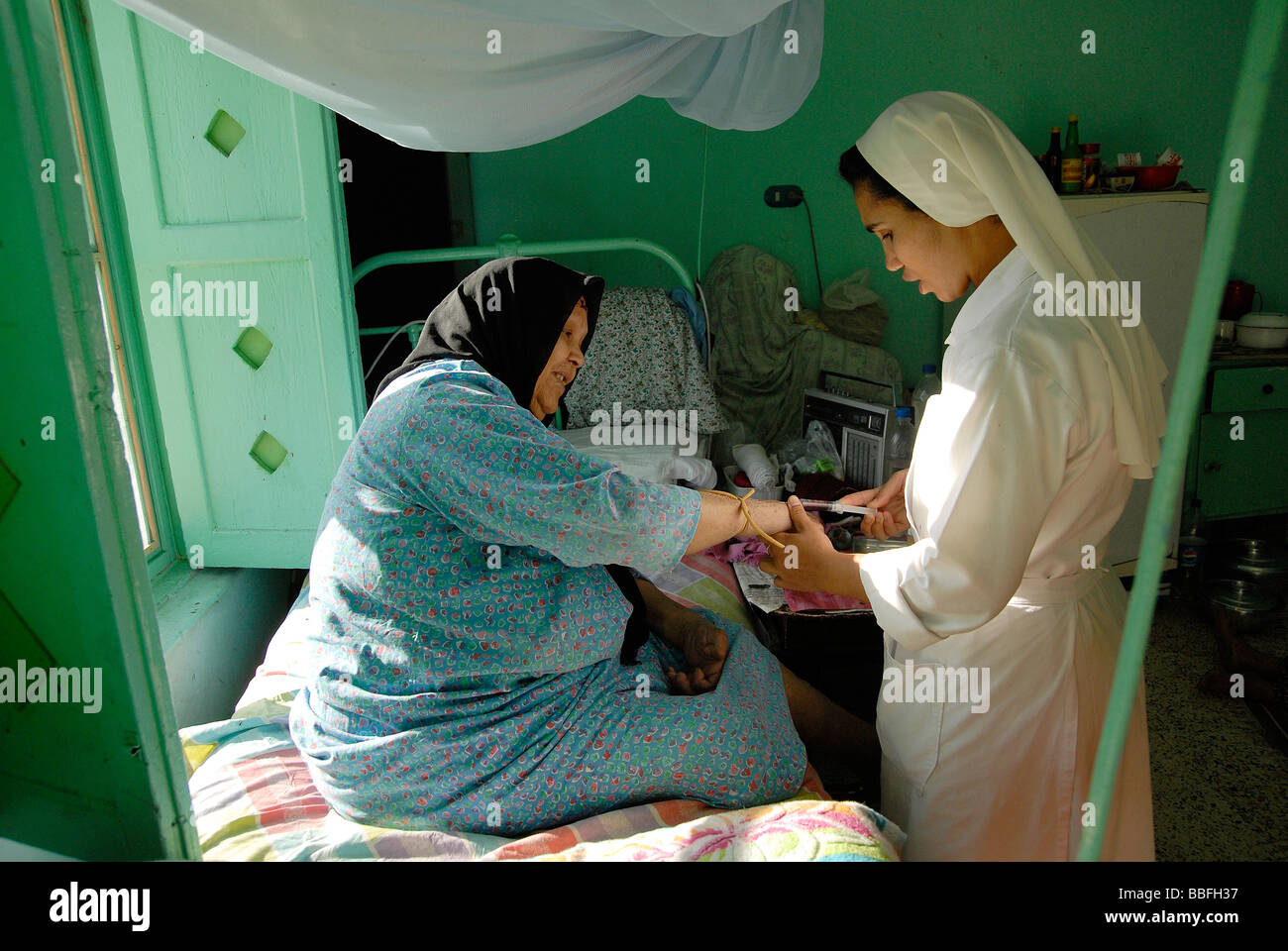 Sister Laura is taking a blood sample of one of the elderly leprosy patients in Egypt's leprosy colony. - Stock Image