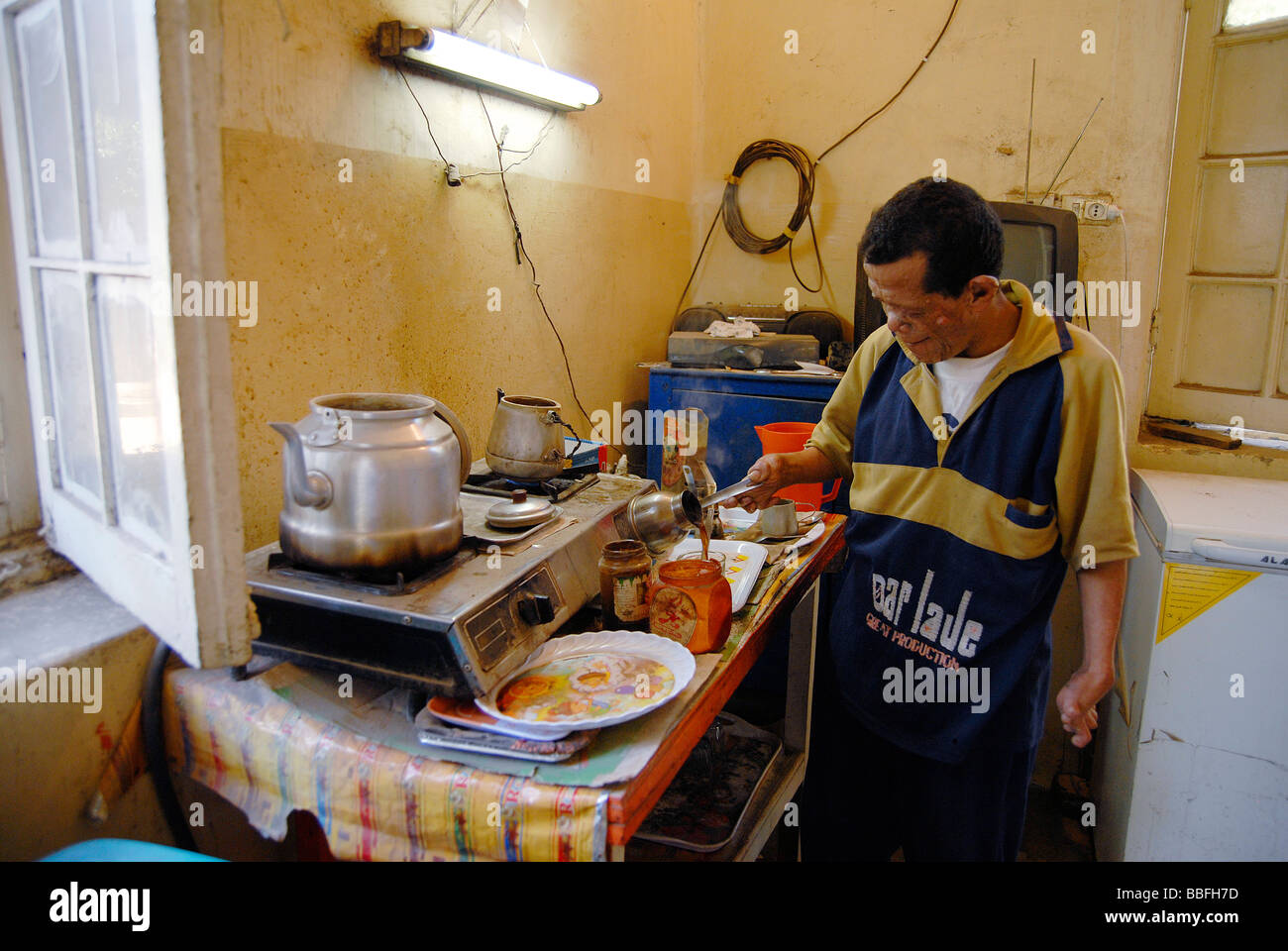 A leprosy patient is running a small cafeteria or coffeshop on the hospital grounds - Stock Image