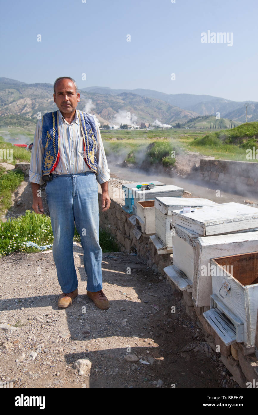 Bee keeper cleaning their wooden hives in a hot stream fed by thermal vents in western Turkey - Stock Image