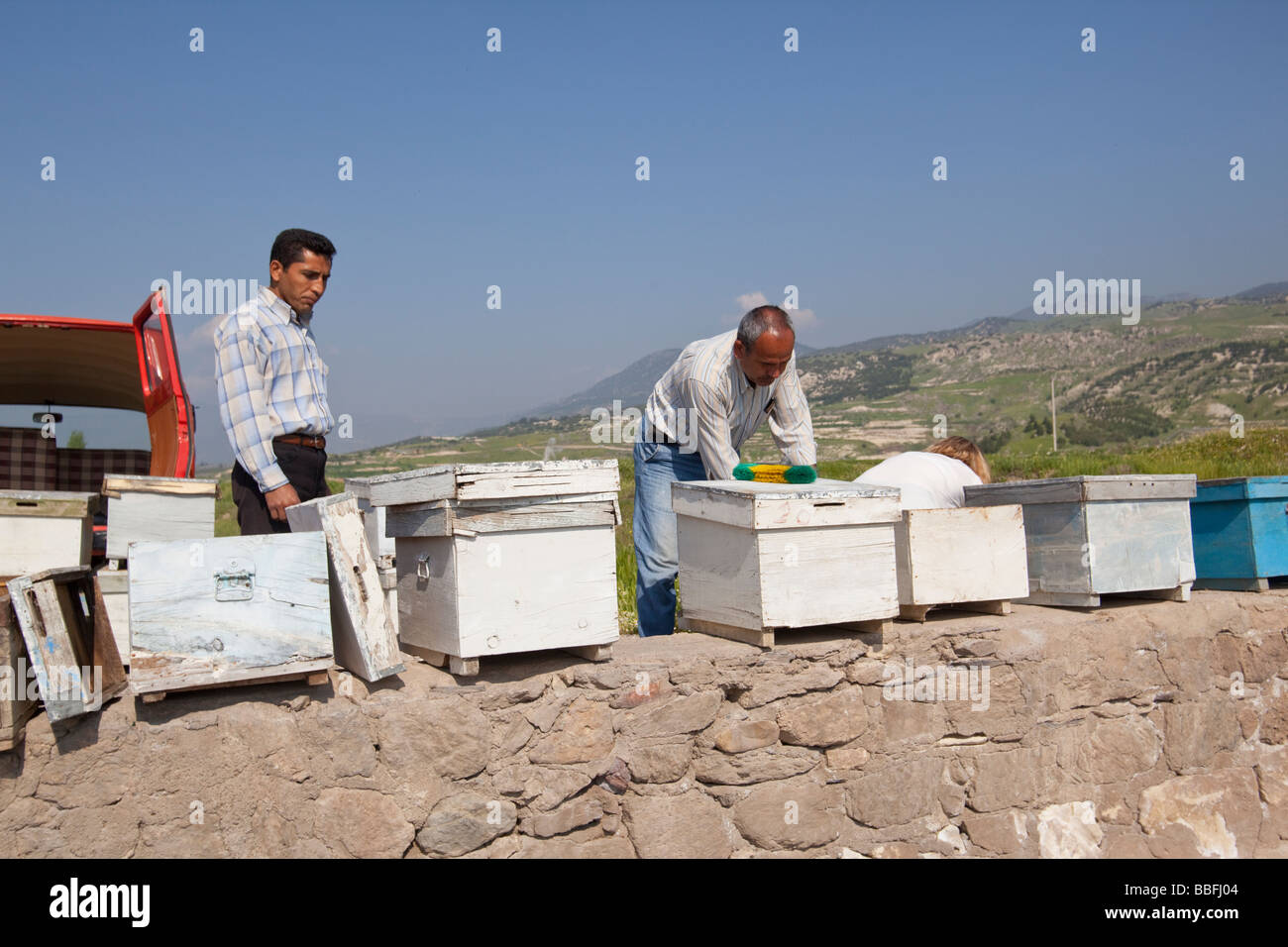 Bee keepers cleaning their wooden hives in a hot stream fed by thermal vents in western Turkey - Stock Image