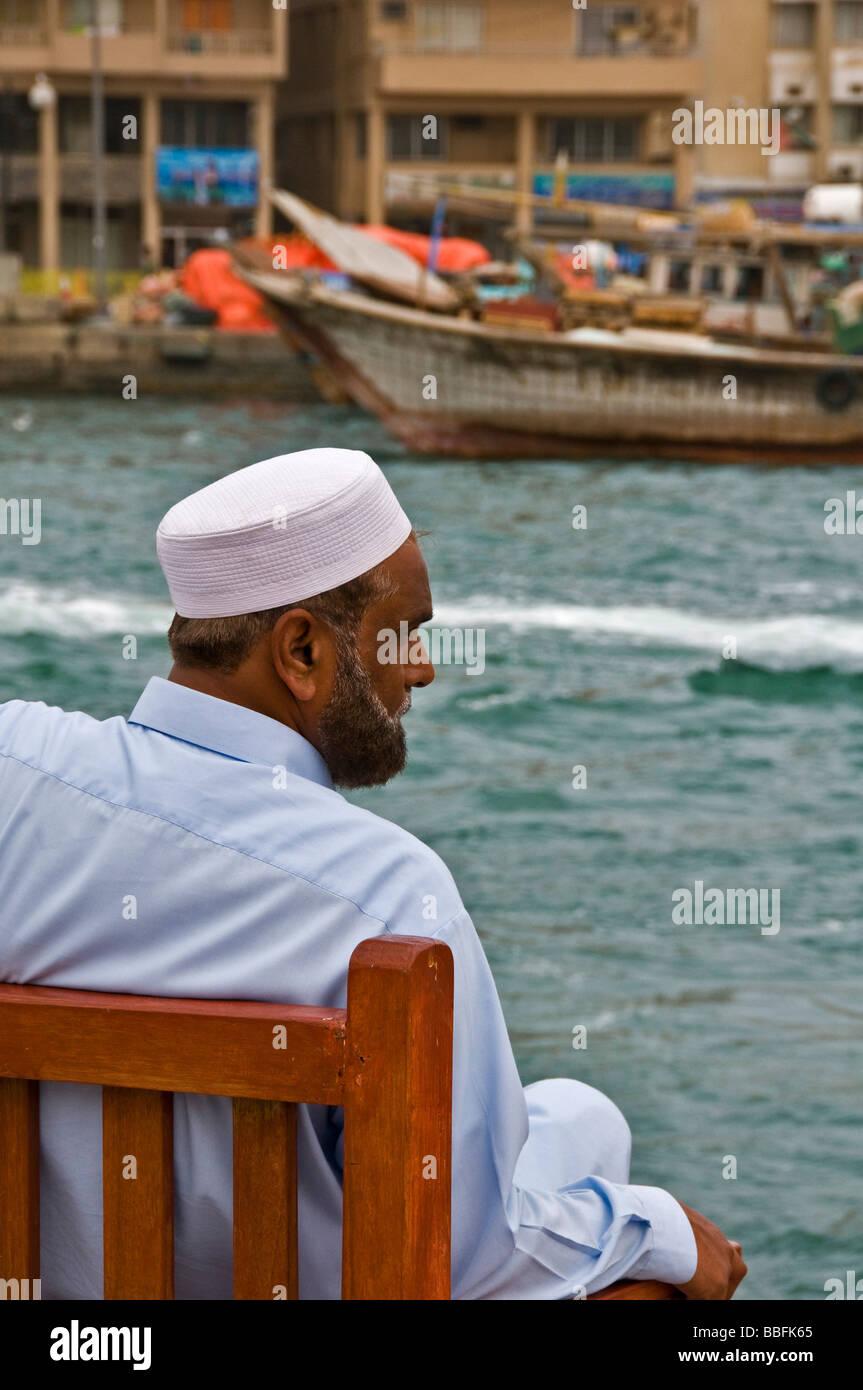 Arab man resting on the Dubai creek - Stock Image