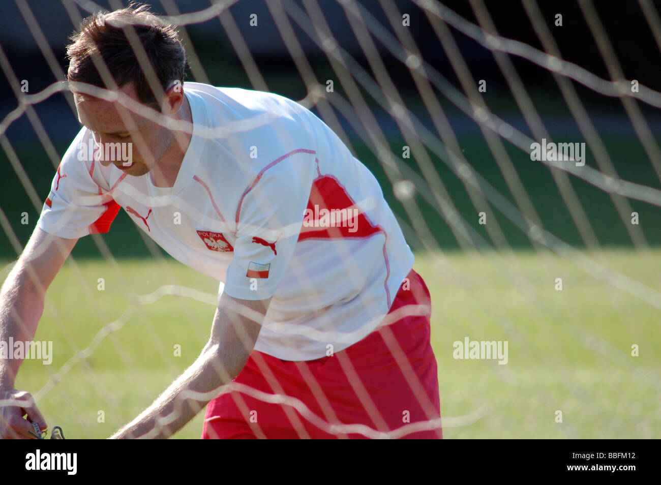 Footballer in Poland kit behind goal net in the summer. - Stock Image
