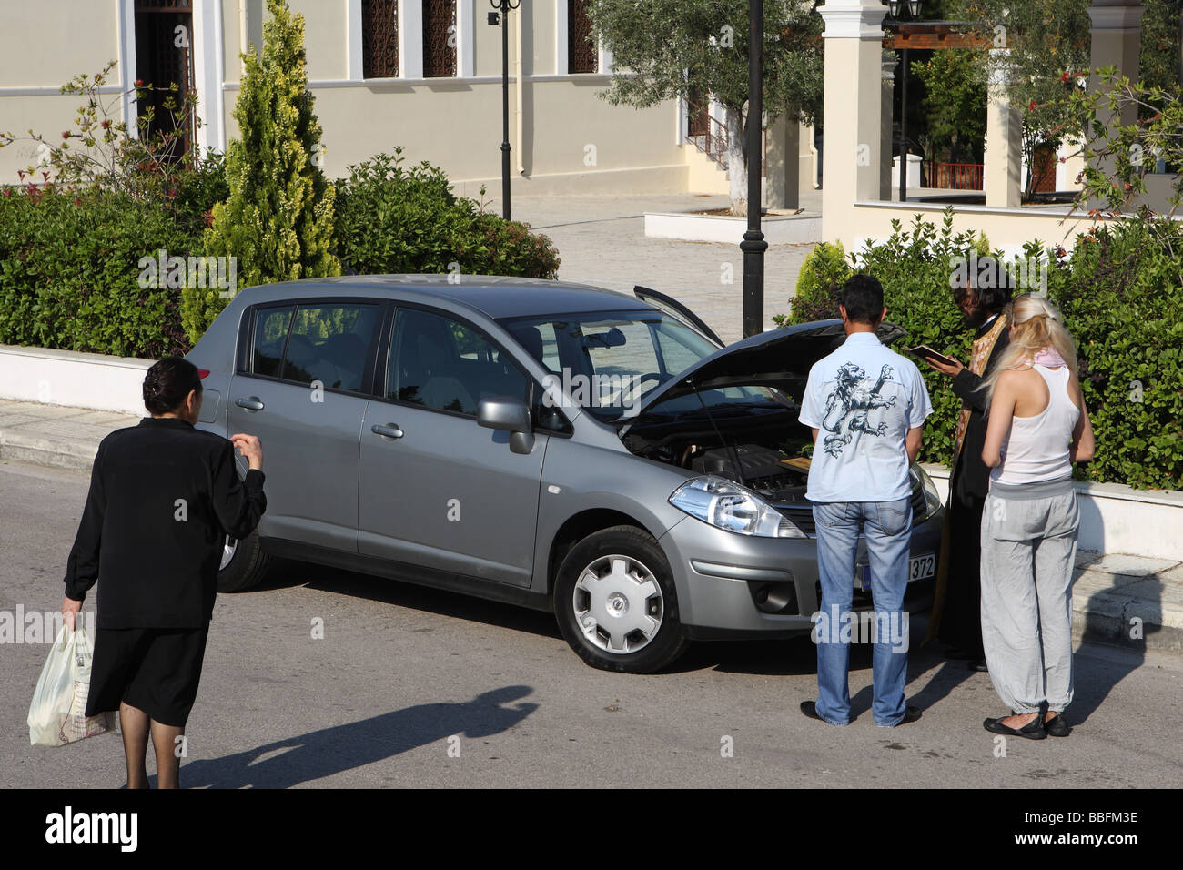 Greek priest blesses a newly bought car while a woman passer by crosses herself Athens Greece - Stock Image