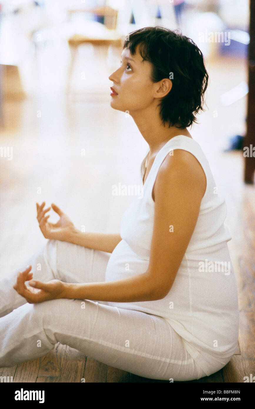 Pregnant woman meditating on floor, side view - Stock Image